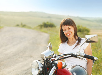 Wall Mural - Young biker woman on the country road