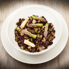 piatto di risotto al nero di seppia con asparagi