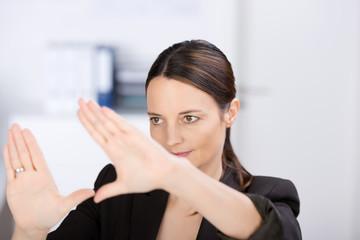 frau im büro bildet einen rahmen mit ihren händen