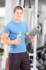 Male posing with refreshment and a mat after an excerise at the