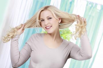 Blonde Frau zieht an ihren langen Haaren
