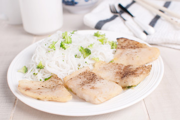 Fish pieces with rice noodles and broccoli