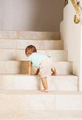 Little girl climbing steps at home