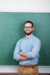 lächelnder mann mit brille steht vor der tafel