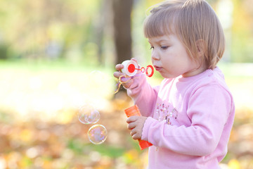 beautiful little girl making  bubble blower on the autumn forest
