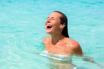 Beautiful young woman enjoying swimming in refreshing sea water
