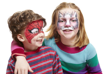 Young boy and girl with face painting of cat and spiderman