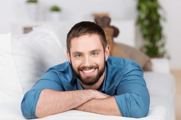 junger mann liegt entspannt auf dem sofa
