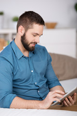 mann mit tablet-pc auf dem sofa