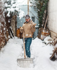Happy woman with snow shovel