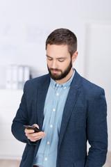 mann im büro schaut auf sein smartphone