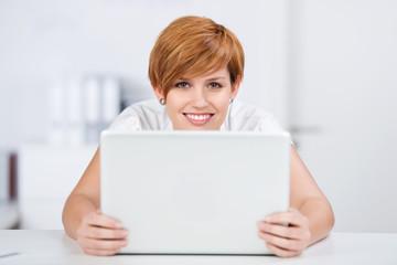 lächelnde frau mit laptop am schreibtisch