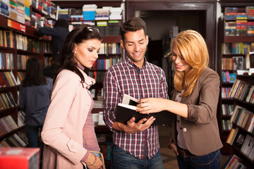 young people reading a book in library