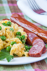 Scrambled eggs with fresh green peas and sausage
