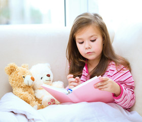 Little girl is reading a story for her teddy bears