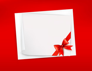 Red background with sheet of paper and red bow and ribbon