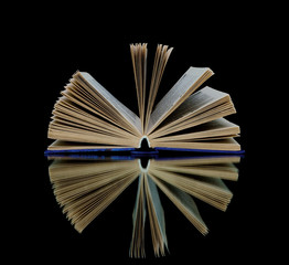 book with reflection on black background