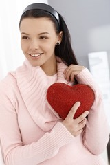 Happy woman holding red heart smiling