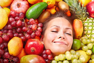 Happy girl in group of fruit.