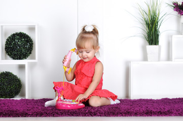 Blonde girl, wearing a dress, talking on the toy phone, calling