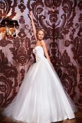 sexy blond bride in white wedding dress in interior