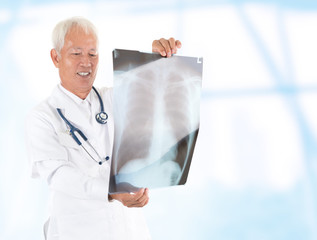 Asian senior doctor checking on x-ray image