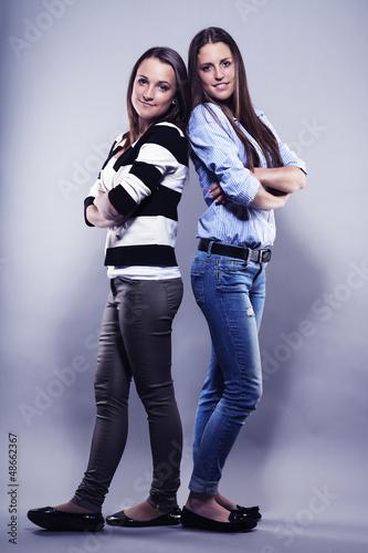 zwei weibliche h bsche teenager stehen r cken an r cken. Black Bedroom Furniture Sets. Home Design Ideas