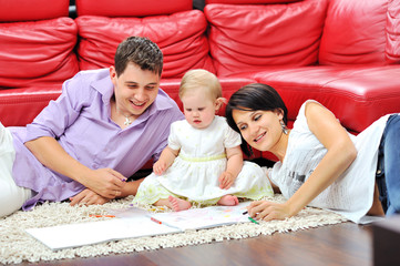Sweet little girl with her parents drawing and having fun