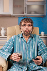drunk man with glass and remote