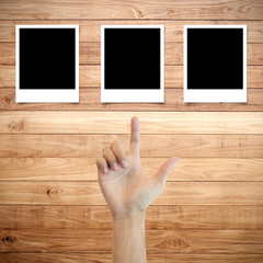 Polaroid photo frame on wood background with hand finger directi