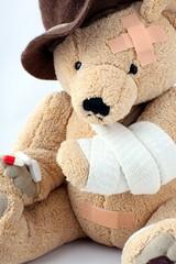Teddy mit berochendem arm hält Pillen in Tatze