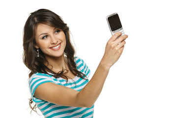 Smiling young woman taking picture of herself through cellphone
