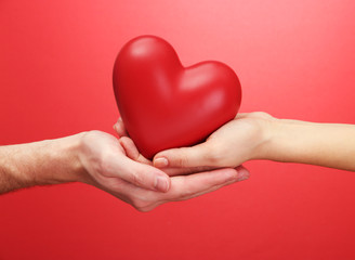 Fototapete - Red heart in woman and man hands, on red background