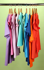 Variety of casual shirts on wooden hangers,on green background