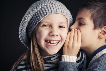 Couple of kids whispering on black background.