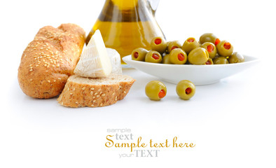 Green olives, oil, slices of bread and cheese are on a white