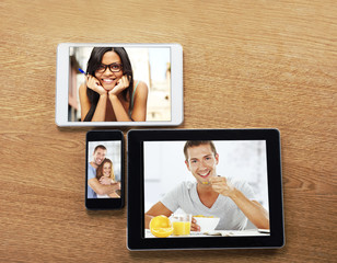 digital tablets and smart phone with images on a desktop