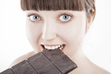 Beautiful young woman eating big chocolate bar