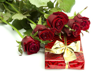 Bouquet of roses and red gift tied up by a bow
