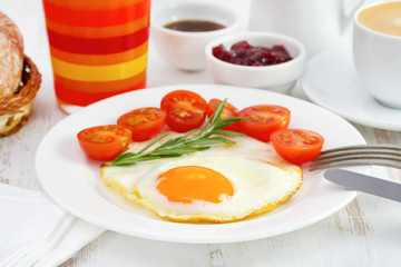 fried egg with tomato and glass of orange juice