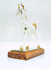 A handicraft glass horse standing on wooden base isolated on whi