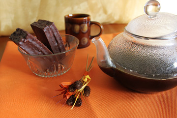 Coffee kettle and bowl with candies on orange cloth