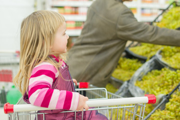 Adorable girl in shopping cart with father select grape in super