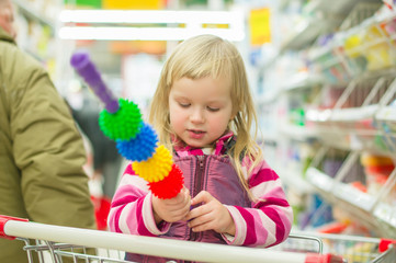 Adorable girl with massage tool in shopping cart in supermarket