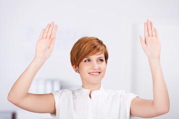lächelnde frau im büro mit händen hoch