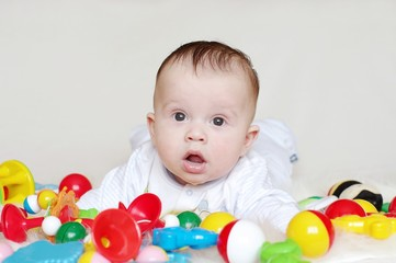 The surprised baby lies on a stomach among toys