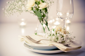 table setting with roses in bright colors and vintage crockery