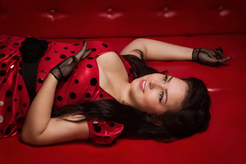 Pin-up girl lying on a red leather couch