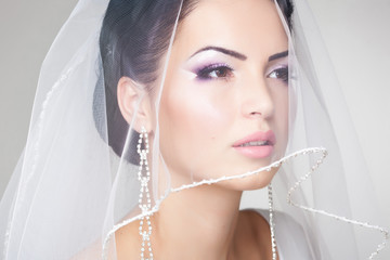 beautiful bride with veil over her face, professional make-up