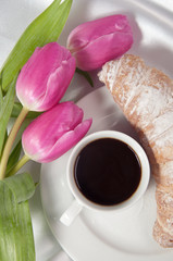 Breakfast with coffee and croissant, tulips on white silk